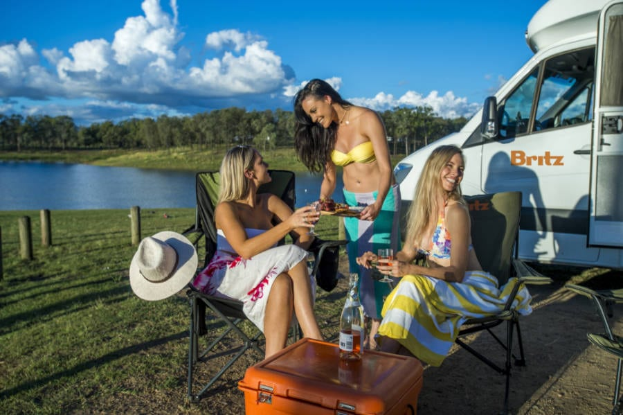 Girls enjoying a picnic outside their Britz Discovery Campervan